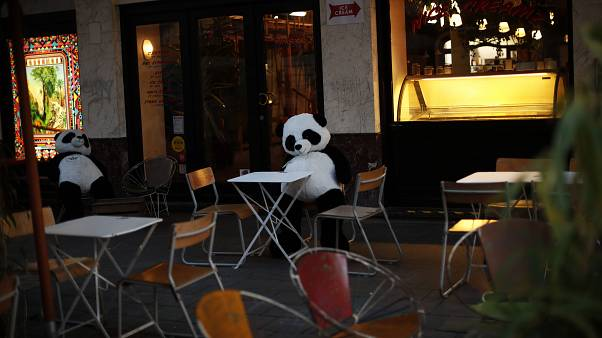 Panda bear cuddly toys rest in an empty terrace of a restaurant in downtown Brussels, Saturday, Oct. 3, 2020.