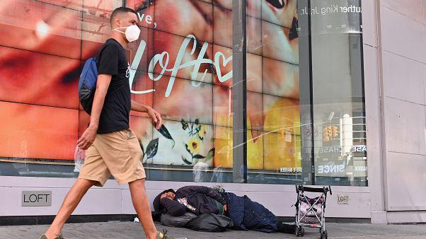 شخص يسير إلى جانب أحد المشردين النائمين في شارع بنيويورك