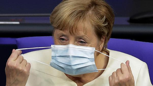 German Chancellor Angela Merkel adjusts her face mask. Berlin, Germany, September 29, 2020.