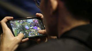 لاعب يلعب على هاتفه الذكي خلال جولات التصفيات لفريق ألعاب الفيديو الإلكترونية الفلبينية في العاصمة مانيلا.