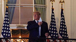 Donald Trump maskesini çıkartırken