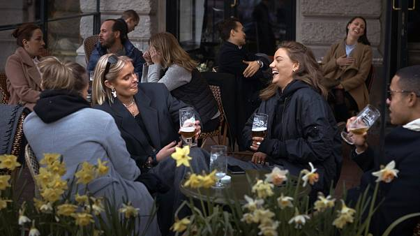 File photo: People chat and drink outside a bar in Stockholm, Sweden, while elsewhere in Europe, citizens were locked down. April 8, 2020.