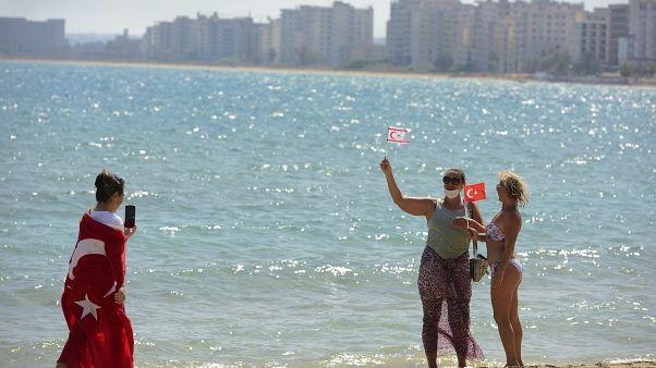 زوار يحملون الأعلام التركية المنفصلة يلتقطون صورًا لبعضهم البعض على الشاطئ مع المباني المهجورة بعد أن فتحت الشرطة شاطئ فاروشا.