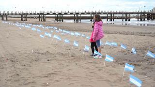 Dos niños argentinos observan las banderas clavadas en la playa Bristol