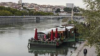 People enjoy a drink on a boat in the centre of Lyon, central France, Thursday, October 8, 2020.