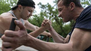 رجلان يتنافسان في مصارعة الأيدي على نهر دنيبرو في كييف، أوكرانيا.