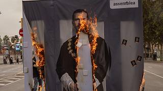 Activists of Catalonia's pro-independence grassroots group, ANC, burn a portrait of Spain's King Felipe VI during a demonstration in Barcelona on Friday, October 9, 2020.