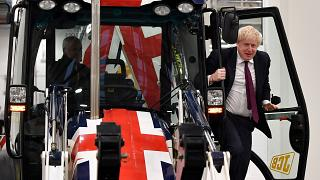 Boris Johnson exits the cab of a Union flag-themed JCB during an election campaign event at the JCB manufacturing plant in Uttoxeter, England, December 10, 2019.
