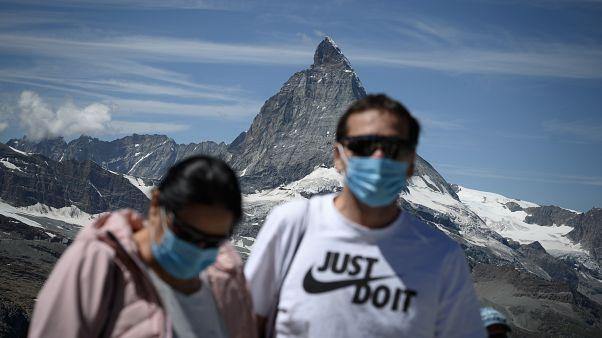 Touristen mit Mundschutz vor dem Matterhorn.