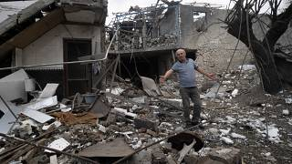 A man gestures in the yard of a house destroyed by shelling by Azerbaijan's artillery during a military conflict in Stepanakert, in Nagorno-Karabakh, Oct. 9, 2020.