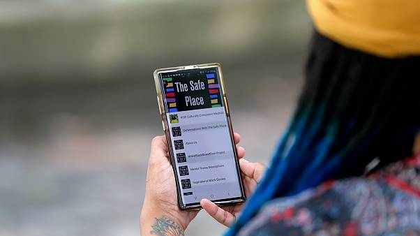 Jasmin Pierre with her smartphone app, a free Black-oriented mental health app that's seen more signups during the pandemic, New Orleans, July 2, 2020.