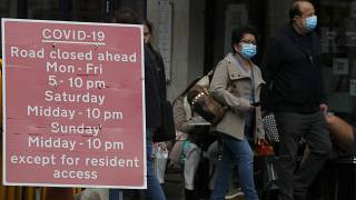 People walk past a sign that refers to COVID-19 closures in London, Friday, Oct. 9, 2020.