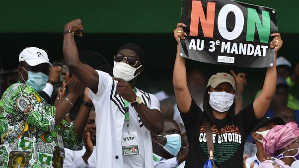 """Ivorian MP Yasmina Ouegnin(R) holds a banner reading """"No to third term"""" during a meeting against the candidacy for re-election of the incumbent president"""