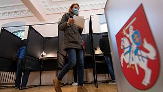 A voter walks past the Lithuanian coat of arms at a polling station during parliamentary elections in Vilnius, Lithuania, Sunday, Oct.11, 2020.