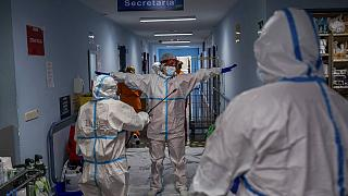 FILE - In this Oct. 9, 2020, file photo, a medical team member is disinfected before leaving the COVID-19 ward at a hospital in Leganes, outskirts of Madrid, Spain.