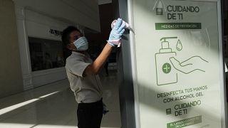 Un hombre desinfecta un panel en el centro comercial Multiplaza de Ciudad de Panamá, 17 de agosto de 2020