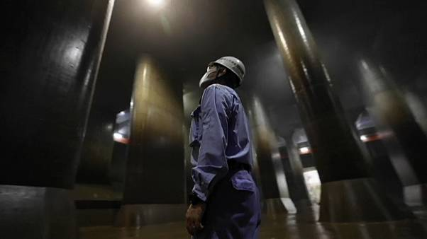 Un operario mira hacia el techo del depósito de Kasukabe