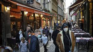 People wearing masks pass by restaurants in Lyon, central France, Saturday, Oct. 10, 2020.