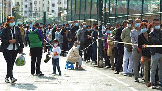 Emberek várnak tesztelésre Csingtaóban