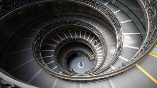 A woman walks down a staircase designed by Giuseppe Momo in 1932, in Vatican Museum