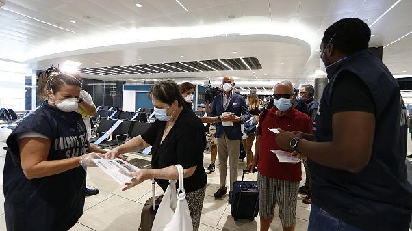 Pasajeros del aeropuerto de Fiumicino en Roma muestran sus informes de test de la COVID-19 al embarcar en un vuelo a Milán, el miércoles 16 de septiembre de 2020.
