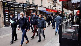 ضباط الشرطة يسيرون في أحد شوارع باريس به مطاعم، خلال دورية لتفقد تنفيذ الإجراءات الصحية الجديدة التي تهدف إلى الحد من انتشار فيروس كورونا المستجد، 6 أكتوبر 2020