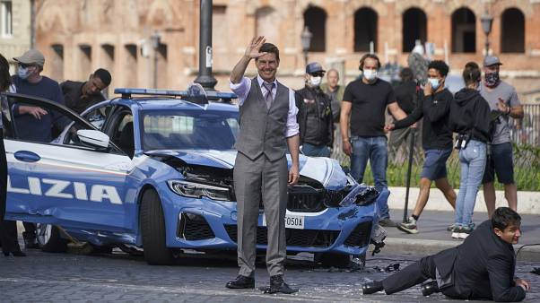 Actor Tom Cruise, center, waves to fans during a break in the shooting of the film Mission Impossible 7, in Rome