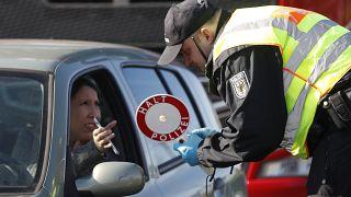 ضابط شرطة ألماني بفحص تصريح دخول امرأة إلى ألمانيا على الحدود الألمانية الفرنسية في كيل ، ألمانيا.