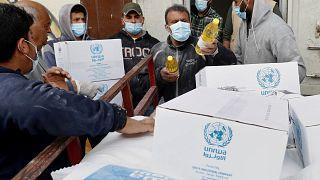 عمال فلسطينيون يقومون بتحميل مواد غذائية توزعتها (الأونروا) في حي الشيخ رضوان بمدينة غزة