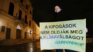 Dr. Bartholy Judit klímakutató tartja a Greenpeace tábláját Orbán Viktor hivatala előtt