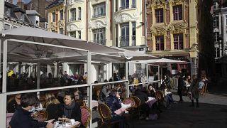 Kávézó teraszán ülő emberek a franciaországi Lille-ben