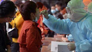 فريق طبي يأخذ عينة لإجراء اختبار كوفيد-19 من امرأة في مقاطعة شاندونغفي شرق الصين. 2020/10/12