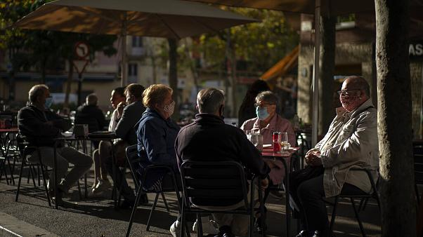 Customers wearing masks to prevent the spread of the coronavirus sit in a terrace bar in Barcelona, Spain,