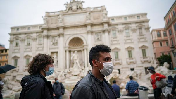 People wear masks by the Trevi Fountain in Rome