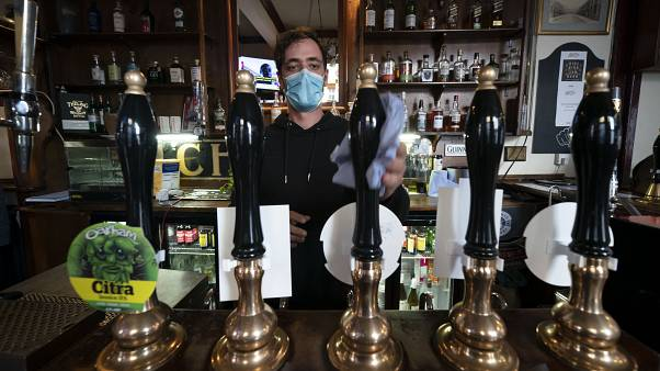 A member of staff cleans beer pumps, at the Dispensary pub in Liverpool, England, Monday Oct 12, 2020.