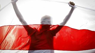 Demonstrator is silhouetted by an old Belarusian national flag during a rally in Minsk, Belarus, Sunday, Oct. 4, 2020