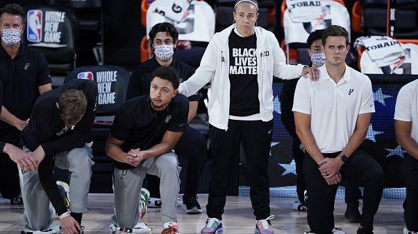 Assistenztrainerin Becky Hammon mit knieenden Spielern der San Antonio Spurs vor einem Match gegen die Memphis Grizzlies im August 2020