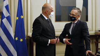 Germany's foreign minister Heiko Maas, right, speaks with his Greek counterpart Nikos Dendias