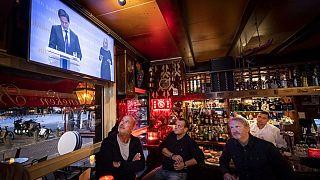 Egy kávézó dolgozói nézik Mark Rutte holland miniszterelnök bejelentését a szigorításokról