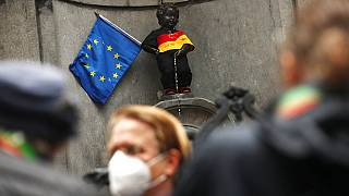 People take photographs of Manneken Pis landmark dressed in the colours of the German flag next to an EU flag in downtown Brussels