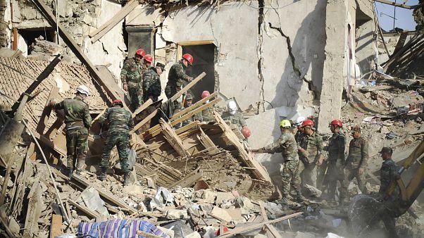 عمال إنقاذ أذريون في موقع تعرض لقصف أرمني في مدينة غنجه