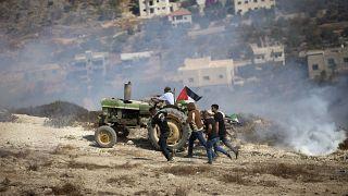 فلسطينيون بالقرب من نابلس يبتعدون عن قنابل مسيلة للدموع أطلقها عليهم الجيش الإسرائيلي
