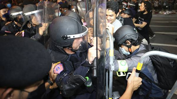 Pro-democracy protesters push Thai policemen with riot shields during a demonstration in Bangkok, Thailand, Thursday, Oct. 15, 2020.