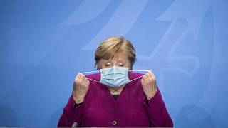 German Chancellor Angela Merkel holds her face mask as she arrives for a press conference after a meeting with the governors of the German states in Berlin, Oct. 14, 2020.