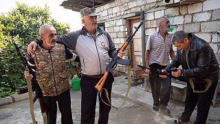 سكان محليون يحملون بنادق كلاشينكوف تلقوها من مكتب التجنيد في بلدة مارتوني، الأربعاء 14 أكتوبر 2020