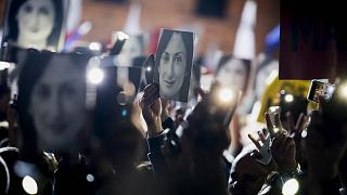 People hold pictures of slain journalist Daphne Caruana Galizia as they protest outside the office of the Maltese Prime Minister Joseph Muscat on Nov. 29, 2019.