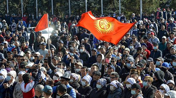 Protesters react waving Kyrgyz national flags as they wait in front of the government building in Bishkek, Kyrgyzstan.