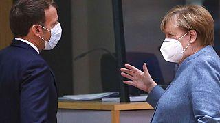 German Chancellor Angela Merkel, right, speaks with French President Emmanuel Macron