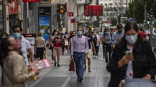 Pedestrians wearing face masks to prevent the spread of coronavirus walk in downtown Madrid, Spain