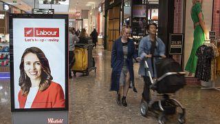 Jacinda Ardern munkáspárti politikus plakátja mellett halad egy pár egy Christchurch-i bevásárlóközpontban